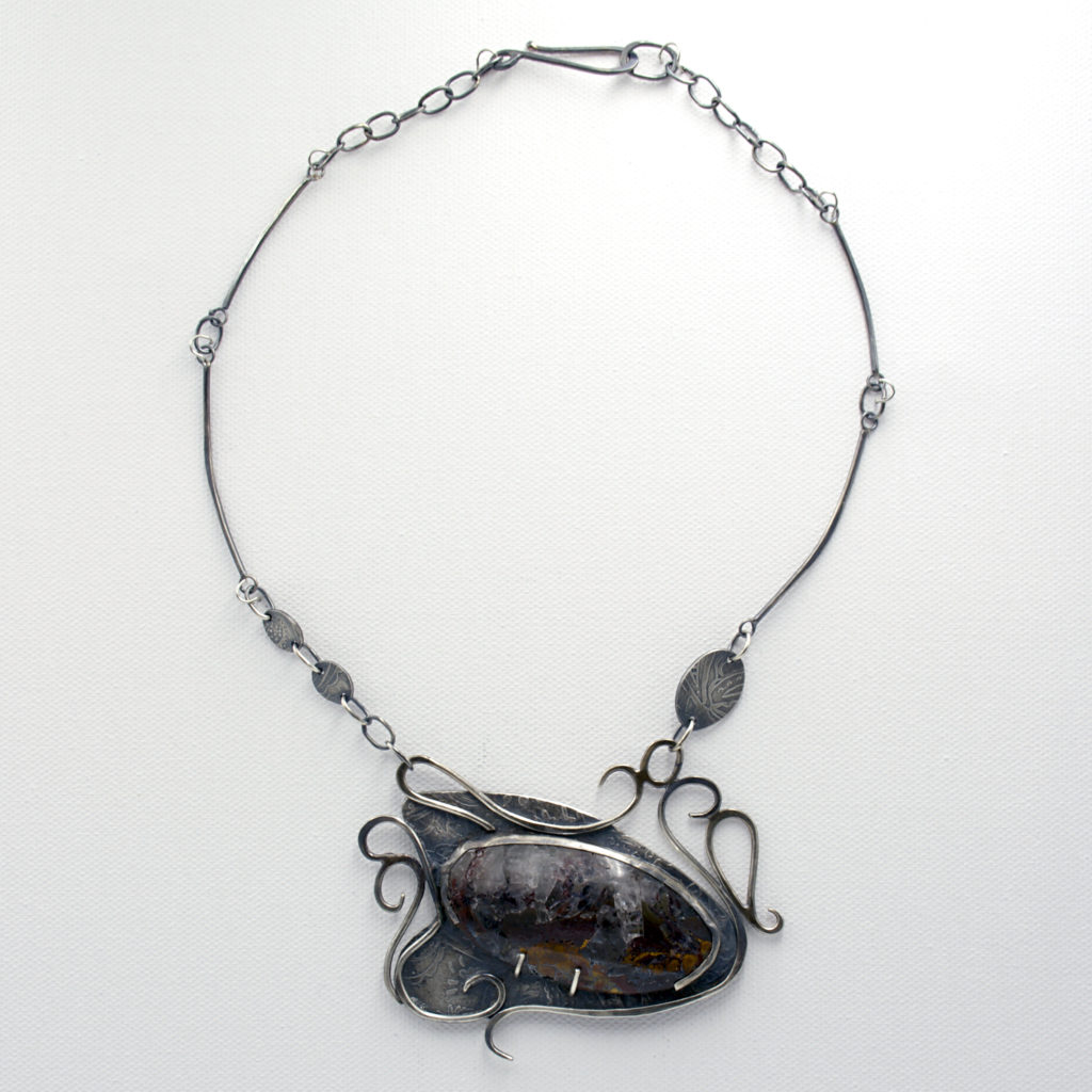 I call her whimsy. Art jewelry piece in sterling silver with hand illustrated metail.